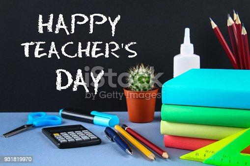 istock Text chalk on a chalkboard: Happy Teacher's Day. School supplies, office, books, apple. 931819970