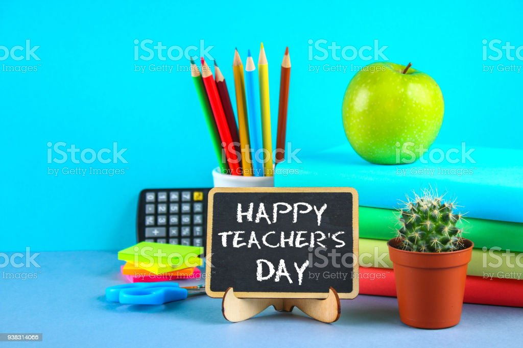 Text chalk on a chalkboard: Happy Teacher's Day. School supplies, office, books, apple. stock photo