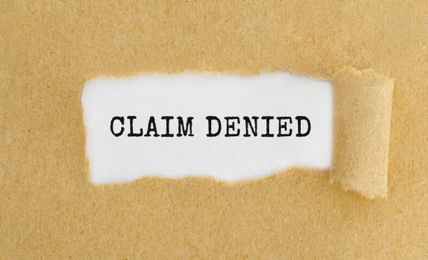 Text Claim Denied appearing behind ripped brown paper stock photo