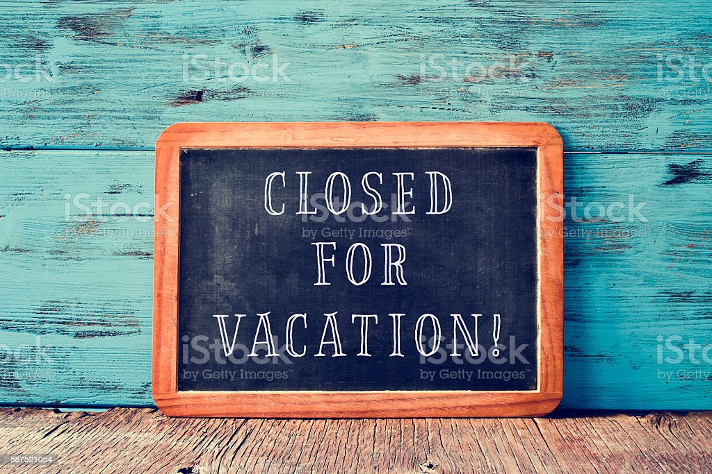 text closed for vacation in a chalkboard stock photo