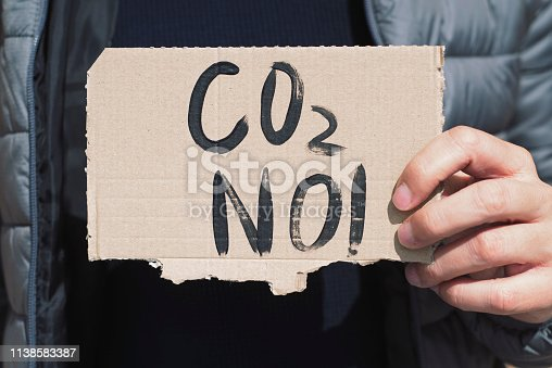 closeup of a young caucasian man, on the street, showing a brown cardboard signboard with the text CO2 no handwritten in it