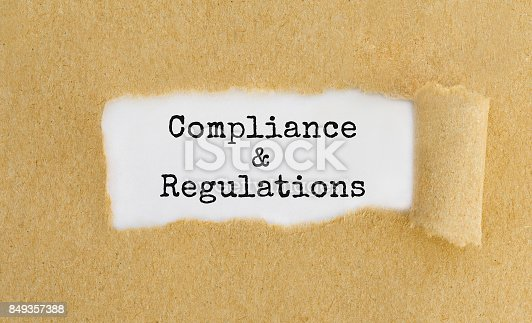 istock Text Compliance and Regulations appearing behind ripped brown paper 849357388