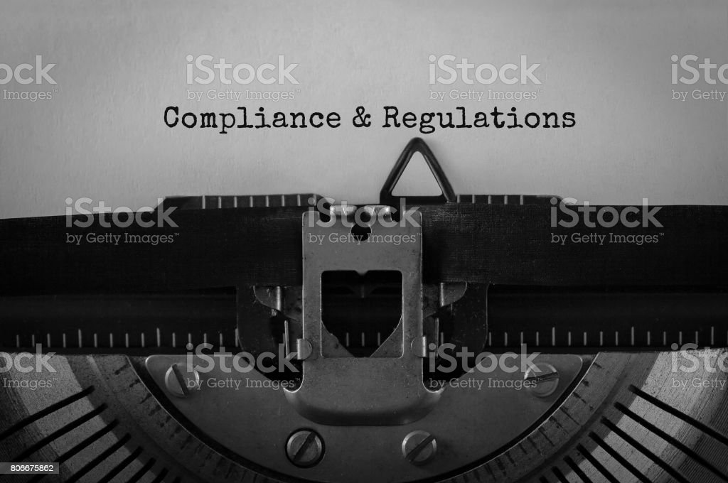 Text Compliance and Regulations typed on retro typewriter stock photo