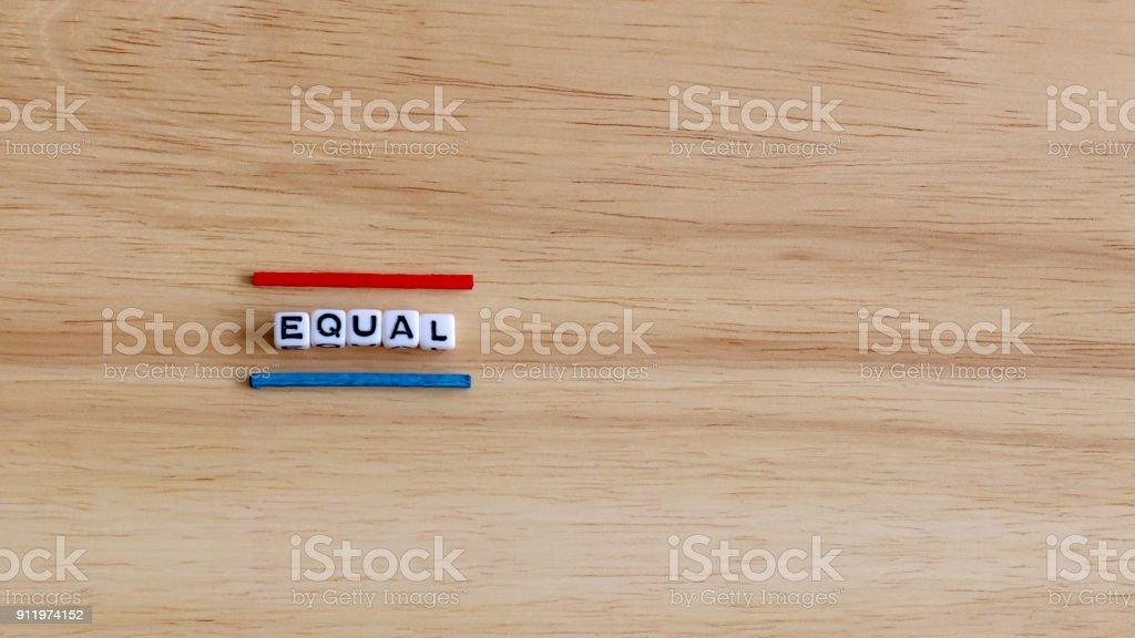 EQUAL text cube and two color stick on the wood background. stock photo