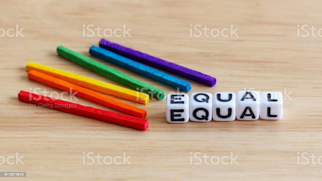 EQUAL text cube and wooden rainbow color stick on the wood background. stock photo
