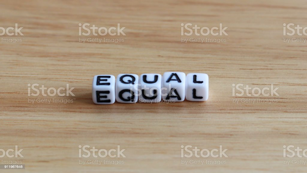 EQUAL text cube on the wood background. stock photo