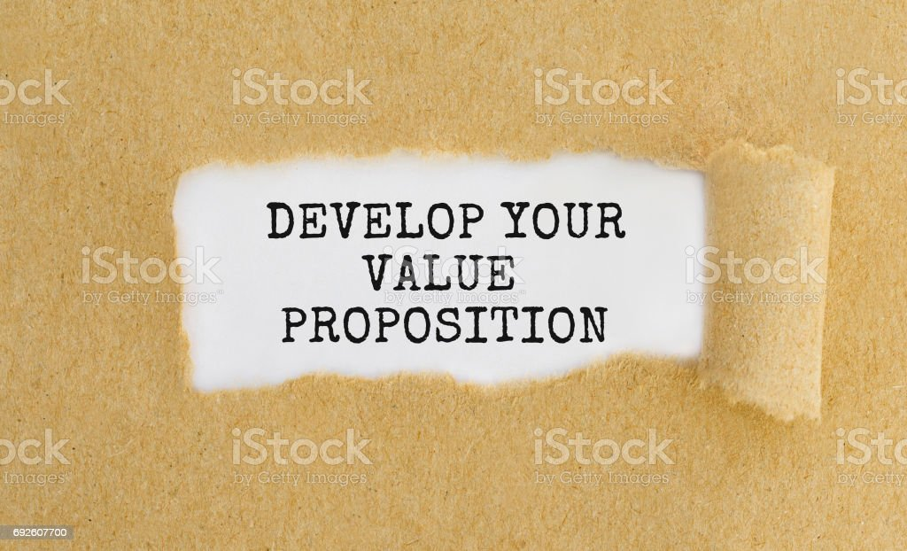 Text Develop Your Value Proposition appearing behind ripped brown paper stock photo