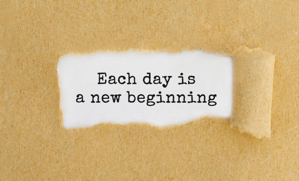 Text Each day is a new beginning appearing behind ripped brown paper stock photo