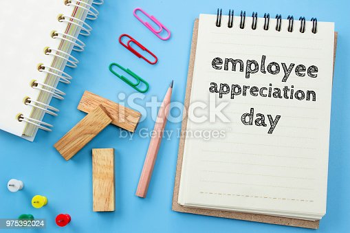 istock Text Employee appreciation day on white paper book and office supplies on blue desk / business concept 975392024