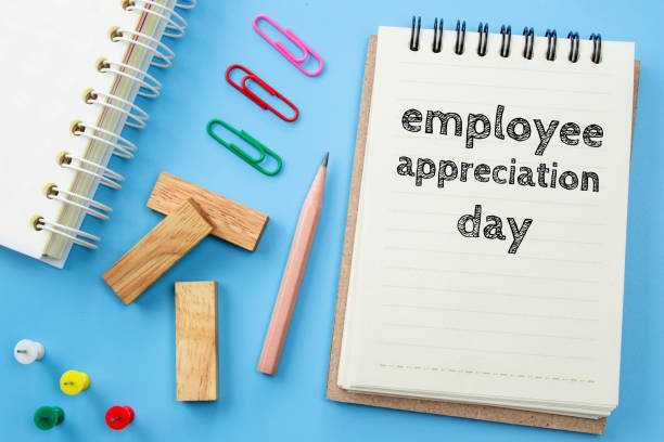 text employee appreciation day on white paper book and office supplies on blue desk / business concept - ammirazione foto e immagini stock