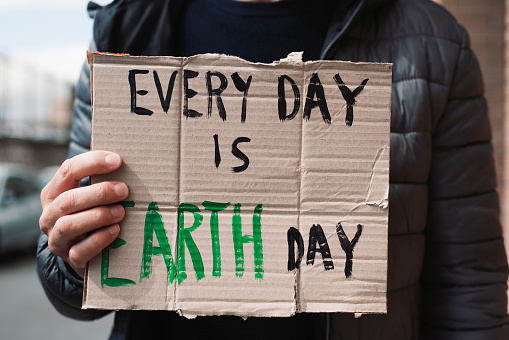 closeup of a young caucasian man, on the street, showing a brown cardboard signboard with the text every day is Earth day handwritten in it