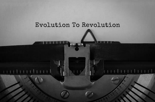 Text Evolution to Revolution typed on retro typewriter stock photo