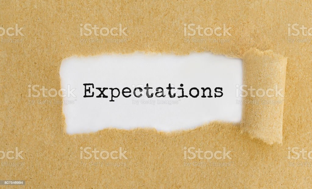 Text Expectations appearing behind ripped brown paper. stock photo