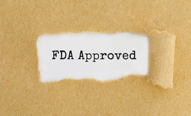 text fda approved appearing behind ripped brown paper. - fda stock photos and pictures