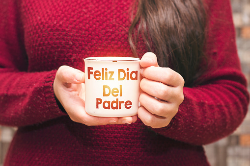 text Feliz Dia Del Padre translated in english happy father's day on cup and woman drinking a coffee