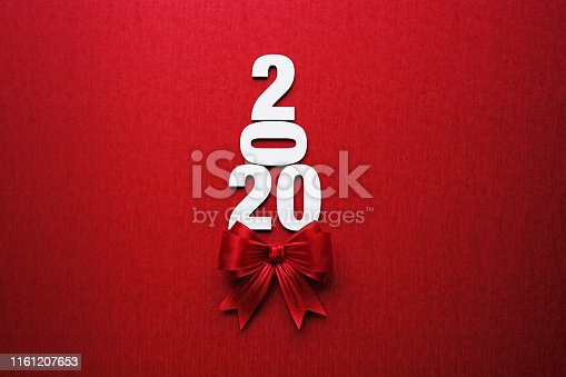 2020 text forming a Christmas tree and is tied with red ribbon on red background. Horizontal composition with copy space. Directly above. Great use for Christmas related gift concepts.