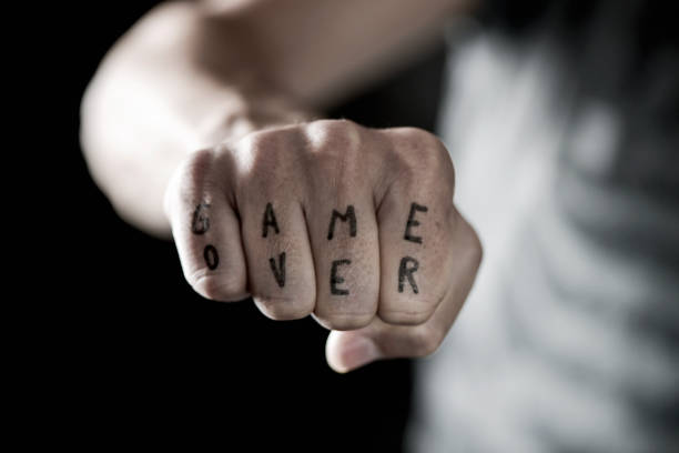 text game over in the knuckles of a young man - knuckle stock photos and pictures