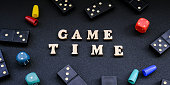 istock Text GAME TIME spelled out in wooden letter. Surrounded by dice, dominoes other game pieces on black background. Table games. Stay home activity 1306464121