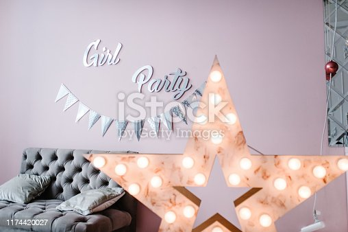 istock Text Girl Party. Silver paper flags garland on pink background wall. Birthday party decoration in room. 1174420027