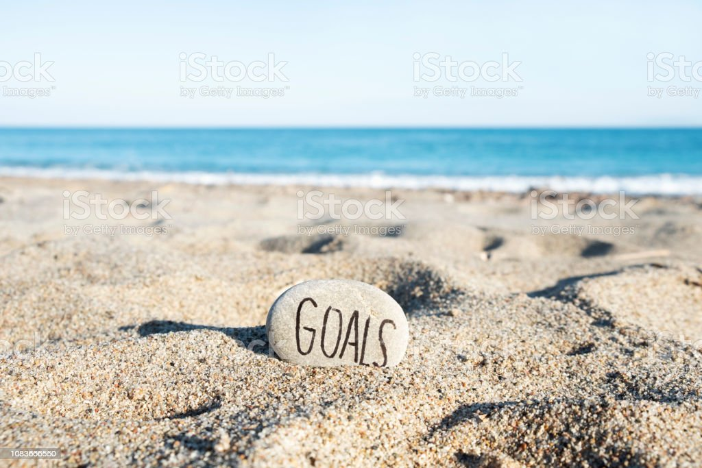 text goals in a stone on the beach stock photo