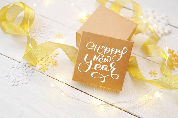 Text Happy New Year auf dem Feld des Handwerks, mit goldenen Bändern und Schneebälle. Fotografie für Urlaub Grusskarte, Einladung, Kalender Poster banner – Foto