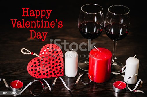 istock Text happy Valentine's Day. A romantic love concept holiday, candles, ribbons, glasses of wine, red hearts on brown wooden background. Place for text. 1091310516