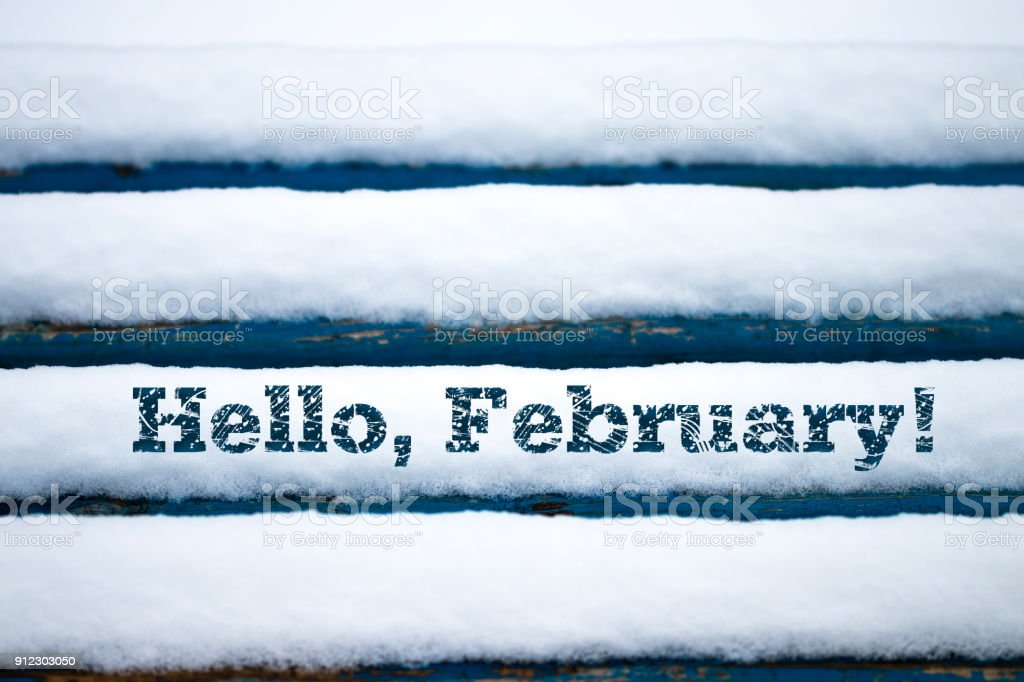 Text Hello February on old wood texture with snow