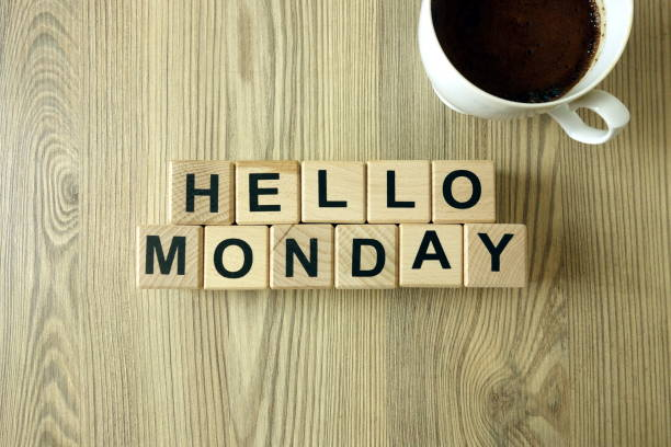 Text hello monday and cup of aromatic coffee on wooden background stock photo