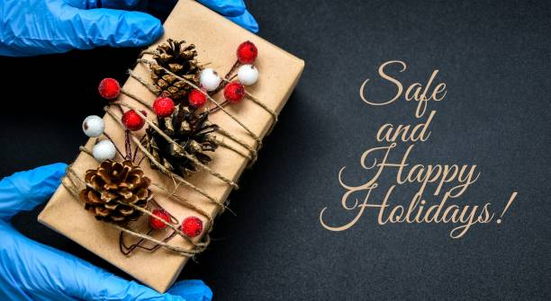 SAFE AND HAPPY HOLIDAYS text Holiday shopping. Festive gifts. Pandemic restriction. Winter shopping. Hand in protective gloves holding present zero waste box. Advertising background. Pandemic. Stay safe stock photo