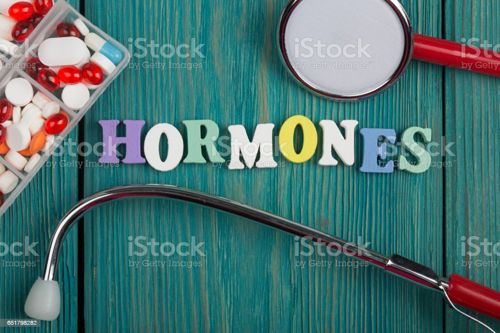 Text 'Hormones' of colored wooden letters, stethoscope and pills stock photo