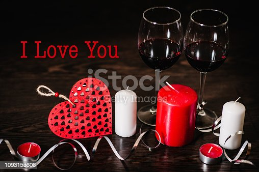 istock Text I love you. A romantic concept holiday, ribbons, candles, glasses of wine, red hearts on brown wooden background. Women's Day, eighth of March. Wedding. St. Valentine's Day. 1093153606