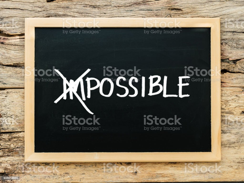 text impossible on black chalk board with cross over on 'im'. possible ,success and challenge concept. stock photo