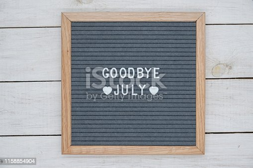 text in English goodbye July and a heart sign on a gray felt Board in a wooden frame. letter Board on white wooden background top view