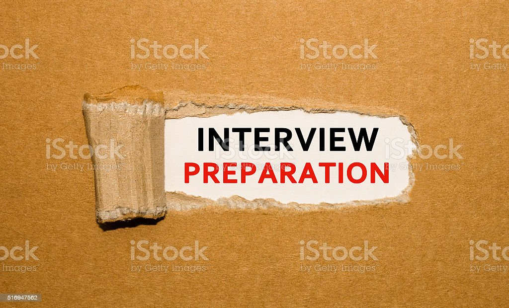 Text Interview Preparation appearing behind torn brown paper stock photo