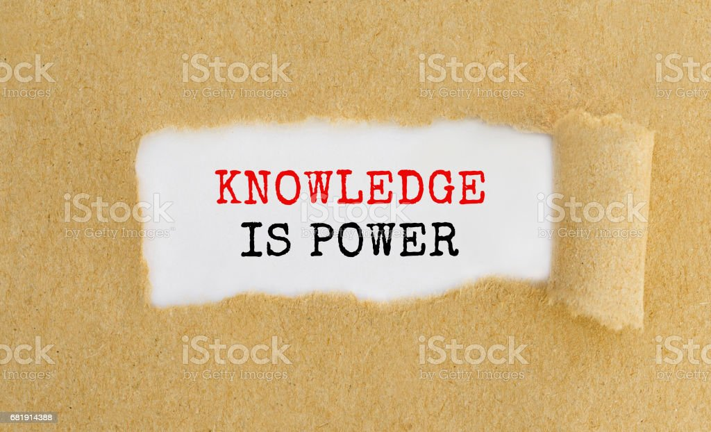 Text Knowledge is power appearing behind ripped brown paper stock photo