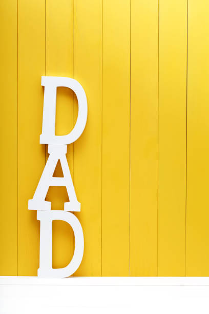 DAD text letters on yellow wooden background stock photo