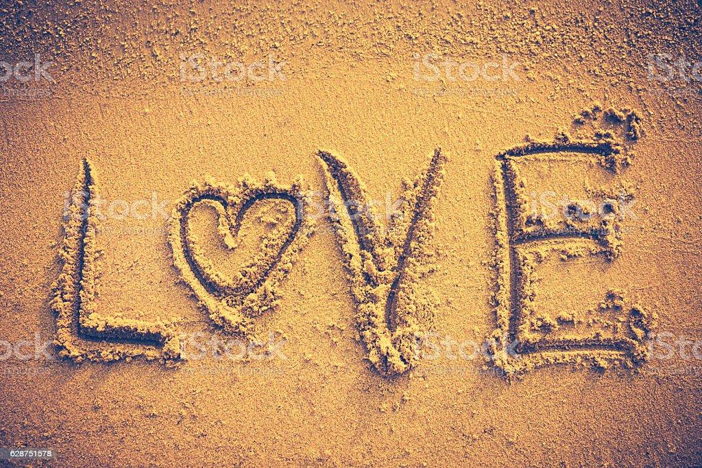 Text LOVE handwritten on seashore sand. Vintage tone. stock photo