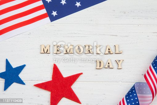 971061452istockphoto Text Memorial Day, stars and American flag. White wooden background 1137110409