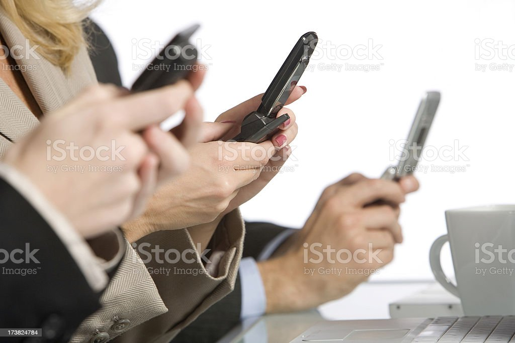 Text Messaging in a Meeting A group of businesspeople text message on their mobile phones. View More: Business Stock Photo