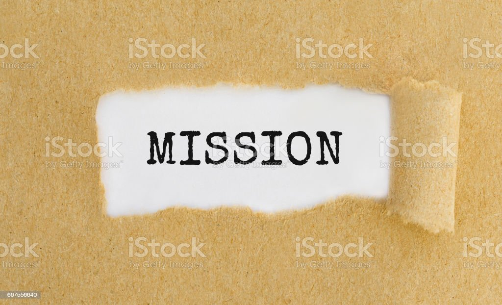 Text Mission appearing behind ripped brown paper. stock photo