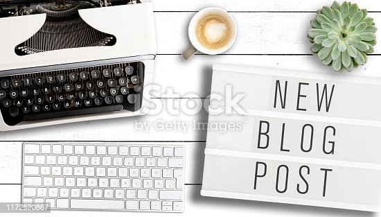 blogging concept, top view of text NEW BLOG POST on light box on table with old typewriter, computer keyboard and cup of coffee