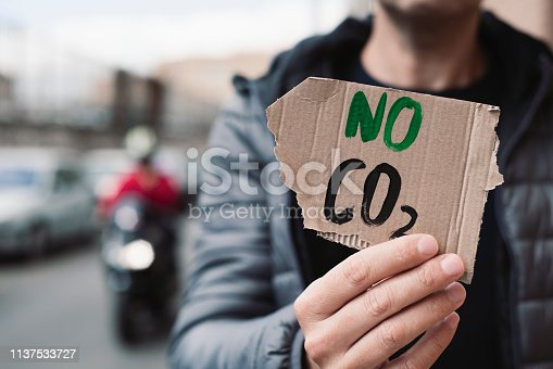 closeup of a young caucasian man, on the street, showing a brown cardboard signboard with the text no CO2 handwritten in it