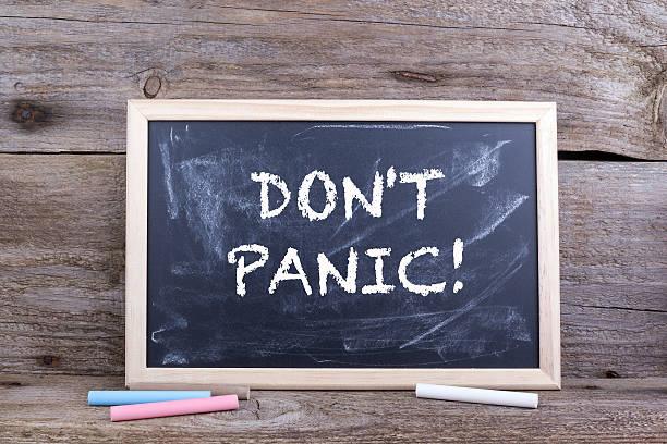 DON'T PANIC! Text on blackboard stock photo