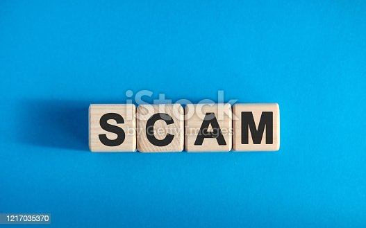SCAM text on wooden blocks, financial business concept, blue background