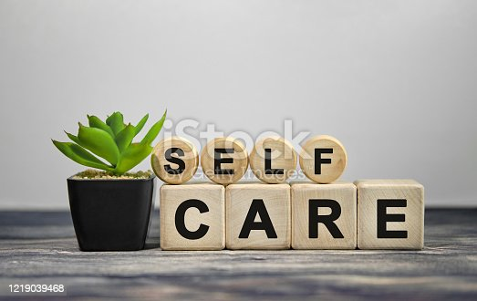 SELF CARE - text on wooden cubes, green plant in black pot on a wooden background