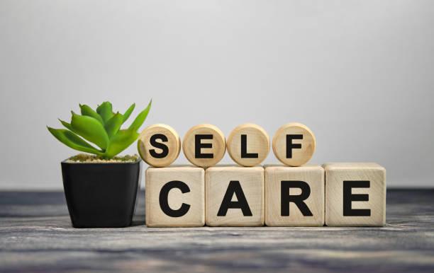 self care - tekst na drewnianych kostkach, zielona roślina w czarnym doniczce na drewnianym tle - wellness zdjęcia i obrazy z banku zdjęć