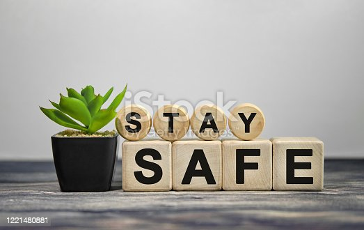 istock STAY SAFE - text on wooden cubes, green plant in black pot on a wooden background 1221480881
