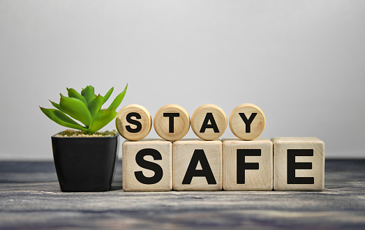 STAY SAFE - text on wooden cubes, green plant in black pot on a wooden background