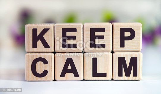 KEEP CALM - text on wooden cubes on a floral background with tulip buds