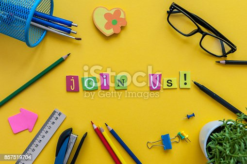 istock JOIN US - CONCEPT text on yellow work place, office background with supplies 857519704